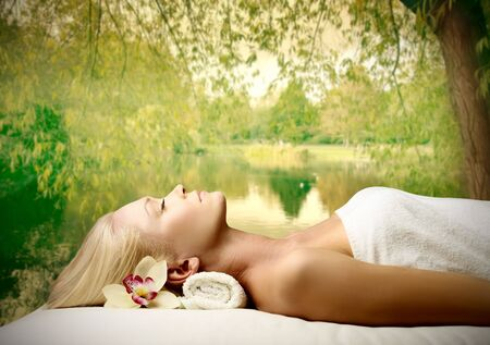 wellness background: Beautiful woman relaxing during a beauty treatment with natural landscape on the background