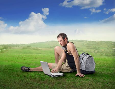 Young man sitting on a green meadow and using a laptop Stock Photo - 7955620