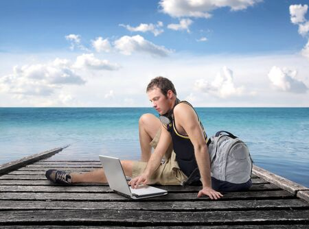 student travel: Young man sitting on a wharf and using a laptop Stock Photo
