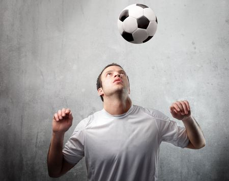 Football player shooting a ball with his head photo