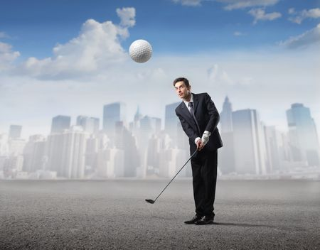 Businessman playing golf with cityscape on the background photo