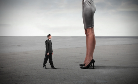 women fight: Tiny businessman standing in front of a giant womans legs Stock Photo