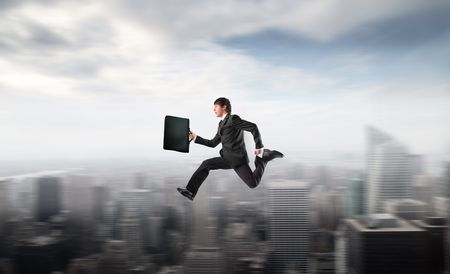 Businessman running fast over a city Stock Photo - 7970112