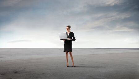 Businesswoman standing in a desert and using a laptop photo