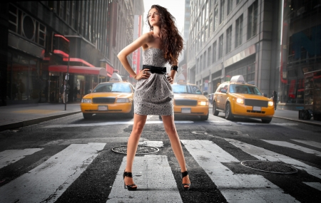 street fashion: Beautiful elegant woman standing in the middle of a city street