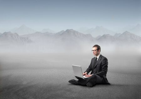 Businessman sitting in the mountains and using a laptop Stock Photo - 8054390