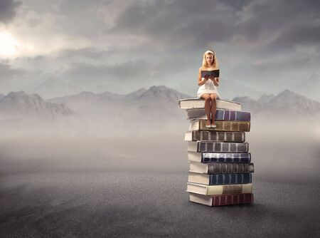 dream land: Young girl sitting ona stack of books and reading Stock Photo