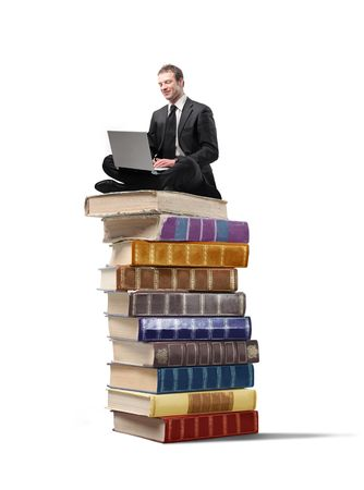 book boy: Businessman sitting on a stack of books and using a laptop