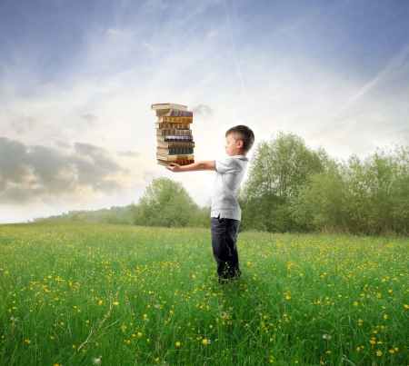 Child standing on a green meadowand holding some books photo
