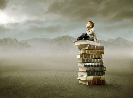 libros: Ni�o sentado sobre una pila de libros en las monta�as  Foto de archivo
