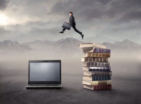 update: Businessman jumping froma stack of books on a laptop Stock Photo
