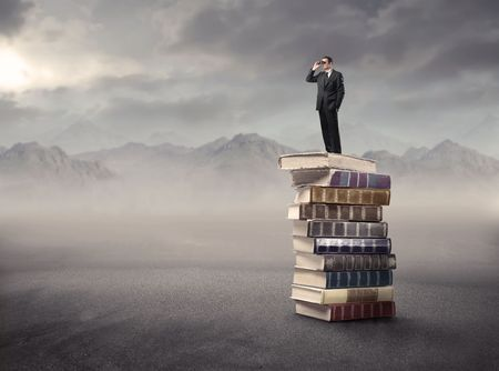 business book: Businessman standing on a stack of books in the mountains and using binoculars Stock Photo
