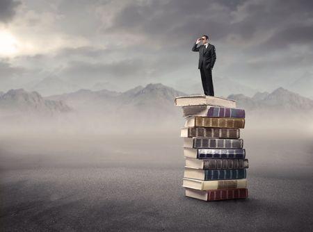 Zaken man staande op een stapel boeken in de bergen en het gebruik van verrekijkers