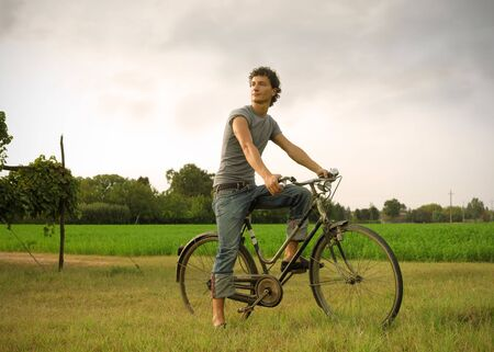 Young man riding a bike in the country Stock Photo - 8054416