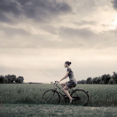 Vintage portrait of a woman riding a bike in the country Stock Photo - 8054413