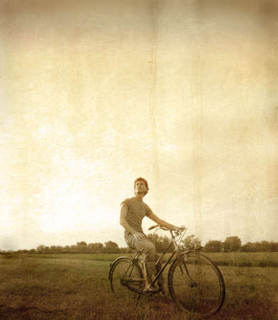 Vintage portrait of a young man riding a bike in the country Stock Photo - 8054414