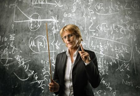 professor: Severe teacher in front of a blackboard Stock Photo