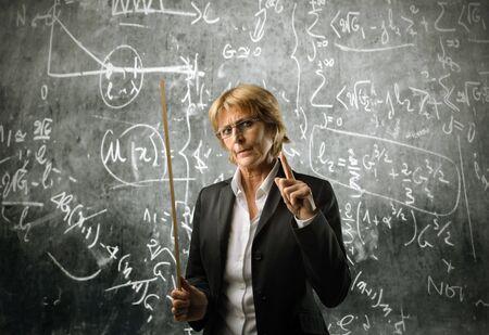 Severe teacher in front of a blackboard