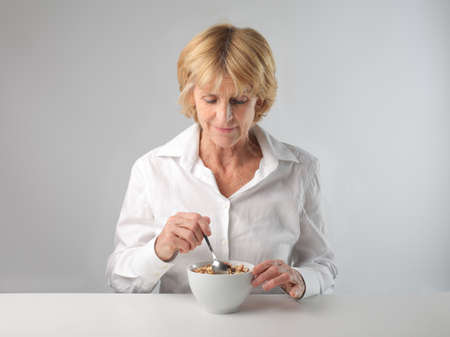 Woman eating cereals for breakfast photo