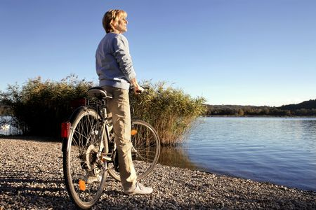 beside: Woman riding a bike beside a lake