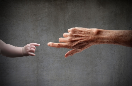 vejez: Mano de Senior tocar la mano de un ni�o  Foto de archivo