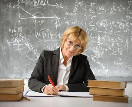Profesor escribir en un registro en un salón de clases