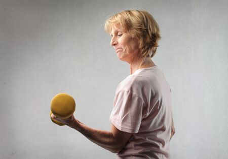 Senior woman lifting weights photo