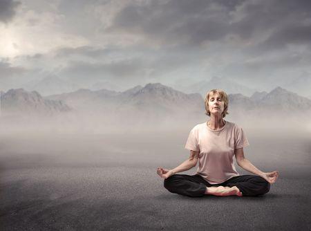 Senior woman meditating on a mountain photo