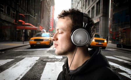 歌: 若い男が都市通りで音楽を聞く 写真素材