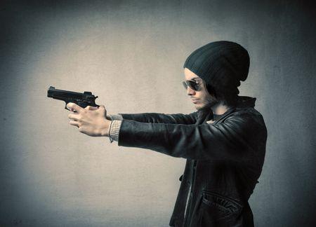 Young criminal pointing a gun photo