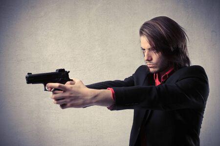 Young man pointing a gun photo