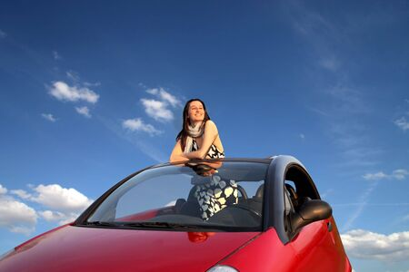 Smiling woman standing in a car Stock Photo - 8054426