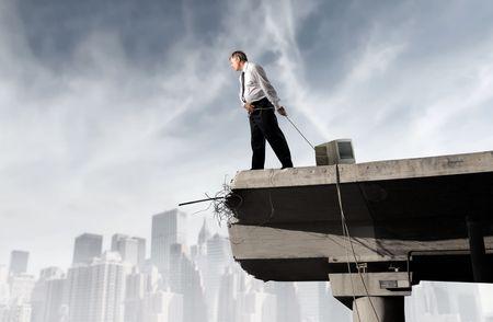 Empresario arrastrando a un monitor de equipo en un puente  Foto de archivo