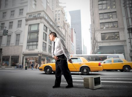 Businessman dragging a computer monitor through a city street Stock Photo - 8054461