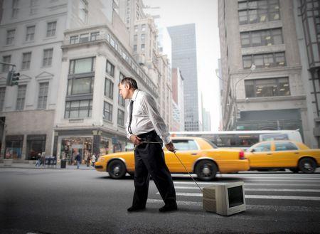 Businessman dragging a computer monitor through a city street Stock Photo - 8054461