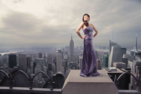 Beautiful woman standing on the rooftop of a skyscraper photo