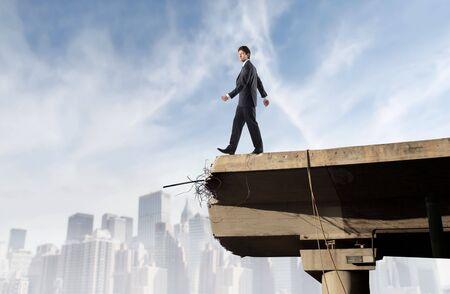 Zaken man lopen naar de leegte op een brug