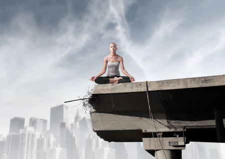 rest in peace: Beautiful woman doing yoga on a bridge with cityscape on the background Stock Photo