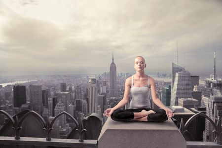 panoramic roof: Beautiful woman doing yoga on the rooftop of a skyscraper Stock Photo