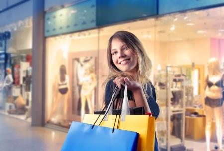 faire les courses: Belle femme transportant des sacs � provisions avec boutiques sur le fond de sourire