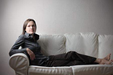 Beautiful woman sitting on a sofa photo