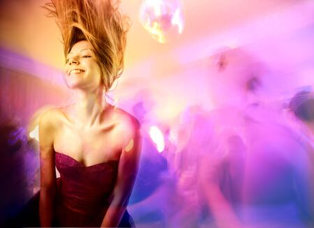 Smiling beautiful woman dancing in a disco photo