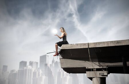 Beautiful woman sitting on the edge of a broken bridge and holding a light in her hands photo