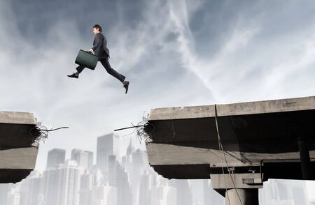 dangerous ideas: Businessman jumping from an edge of a broken bridge to another Stock Photo