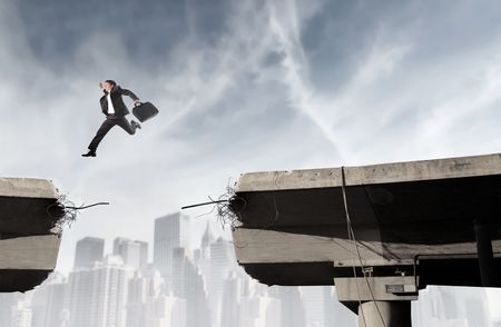 Businessman jumping from an edge of a broken bridge to another photo