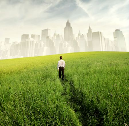 escape: Businessman walking on a green meadow with cityscape on the background