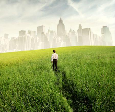 huir: Empresario caminando sobre un prado verde con paisaje urbano en el fondo  Foto de archivo