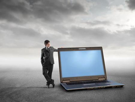 Businessman standing beside a laptop