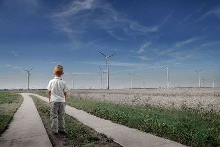 Child standing in front of an installation of windmills photo