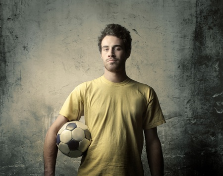 jugadores de futbol: Jugador de f�tbol sosteniendo un bal�n de f�tbol Foto de archivo